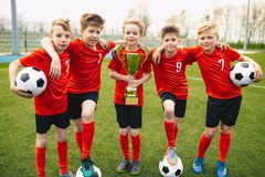 Happy Young Boys In Football Team. Kids in School Soccer Sports Team Holding Golden Trophy and Soccer Balls. Group Of Children In Soccer Team Having Fun After royalty free stock images