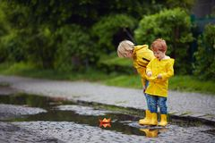 Happy young boys, friends playing in spring puddles with colorful paper boats royalty free stock images