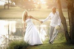 Happy young bridal couple flirting under tree beside lake Stock Image