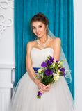 Happy young bride with bouquet in white studio Royalty Free Stock Photos