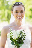 Happy young bride with flowers in garden Royalty Free Stock Images
