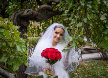 Happy young bride in a green garden Royalty Free Stock Photo