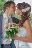 Happy young bride and groom embrace and kiss Stock Images