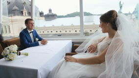Happy young bride and groom in love sitting and posing in a cafe with panoramic city view. Wedding day concept stock video