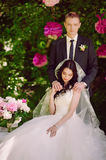Happy young bride and groom in a pink decorated with peonies area in nature, family, relationships, romance, smiles, hugs, love, l Stock Photo