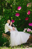 Happy young bride and groom in a pink decorated with peonies area in nature, family, relationships, romance, smiles, hugs, love, l Stock Image