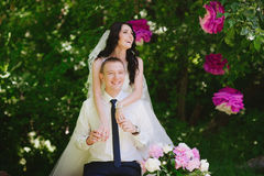 Happy young bride and groom in a pink decorated with peonies area in nature, family, relationships, romance, smiles, hugs, love, l Stock Photography