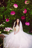 Happy young bride in a pink zone decorated with peonies in nature, family, relationships, romance, smiles, hugs, love, lifestyle Stock Images