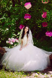 Happy young bride in a pink zone decorated with peonies in nature, family, relationships, romance, smiles, hugs, love, lifestyle Royalty Free Stock Photos