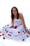 Happy young bride with rose petals. A beautiful smiling bride sitting on a white background with red rose petals stock photography