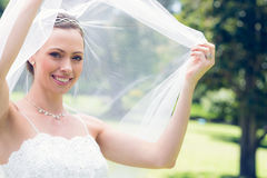 Happy young bride unveiling self in garden Royalty Free Stock Photos