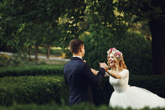 Happy young bride in white dress running towards groom outdoors Stock Photography