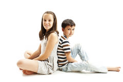 Happy young brother and sister posing back to back sitting on floor Royalty Free Stock Photography