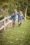 Happy Young Brother and Sister Running Outside Royalty Free Stock Photos