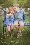 Happy Young Brother and Sister Sitting Together Outside Stock Image