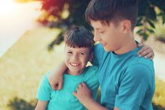 Happy young brothers have fun outdoor in sunset. Happy young caucasian brothers have fun outdoor in sunset royalty free stock image
