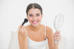 Happy young brown haired model in white pajamas applying powder on her face Royalty Free Stock Photo
