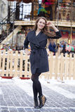 Happy young brown haired woman on the background of a winter amu Royalty Free Stock Images