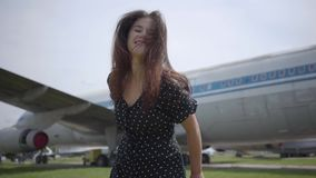 Happy young brunette girl dancing and spinning around looking at the camera in front of the big white plane, the hair stock video
