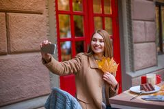 Happy girl in cafe making selfie on mobile phone holding autumn foliage. Outside. stock photography