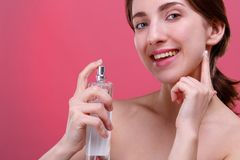 Happy girl, applying perfume with a bottle and cute smiling. On a pink background. Close-up. royalty free stock image