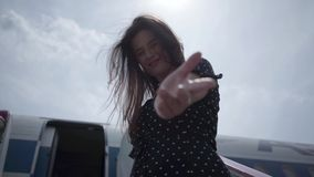 Happy young brunette girl with fluttering hair making inviting gesture looking at camera in front of the plane. Joy of. Happy young brunette girl with fluttering stock footage
