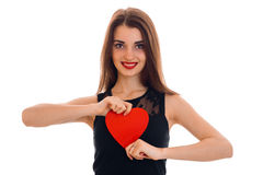 Happy young brunette girl posing with red heart isolated on white background. Saint Valentines Day concept. Love concept Royalty Free Stock Photography