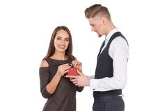 A happy girl takes a gift from her boyfriend. Valentine`s Day. Isolated on white background. Royalty Free Stock Photography