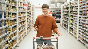 Pretty guy with a phone and a food basket dancing in the supermarket stock video footage
