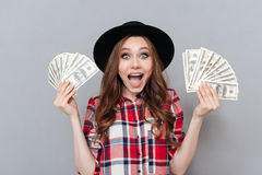 Happy young brunette lady holding money. Royalty Free Stock Photography