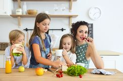 Happy young brunette mother with cute little kids having breakfast royalty free stock photography