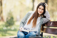 Happy young brunette with a notebook in hands sitting on a park bench Royalty Free Stock Photography
