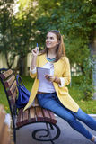 Happy young brunette sitting on a park bench Royalty Free Stock Image