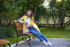 Happy young brunette sitting on a park bench Royalty Free Stock Photography