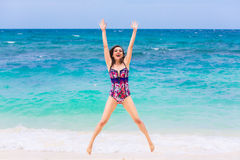 Happy young brunette in a swimsuit on a tropical beach. Blue sea Stock Photo