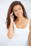 Happy young brunette talking her mobile phone Royalty Free Stock Images