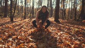 Adolescent girl is playing with dry foliage in forest, throwing up in air. Happy young brunette is tossing yellow leaves in air in park in sunny fall day. She is stock video footage