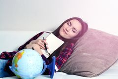 Happy young brunette woman dreams of a journey vacation lying on a white sofa with a diary.  Royalty Free Stock Photography