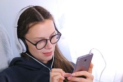 Happy young brunette woman in glasses and headphones talk a video chat on a mobile phone. stock images
