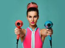 Happy young brunette woman with hair dryer on blue mint background. Hair style beauty concept royalty free stock images