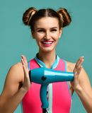Happy young brunette woman hold green hair dryer smiling on blue mint background. Hair style beauty concept Stock Photo