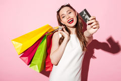 Happy young brunette woman holding credit card and shopping bags Stock Image