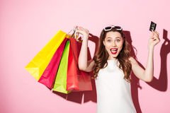 Happy young brunette woman holding credit card and shopping bags. Image of a happy young brunette woman in white summer dress holding credit card posing with Royalty Free Stock Photo