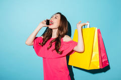 Happy young brunette woman holding shopping bags talking by phone. Picture of a happy young brunette woman in pink dress posing and looking aside over blue Stock Photos