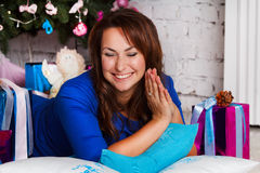Happy young brunette woman opening gift box near christmas tree Royalty Free Stock Photos