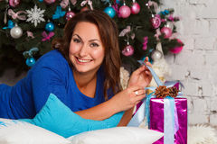 Happy young brunette woman opening gift box near christmas tree Stock Image