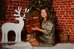 Happy young brunette woman opening gift box near christmas tree Royalty Free Stock Images