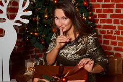 Happy young brunette woman opening gift box near christmas tree Royalty Free Stock Photography