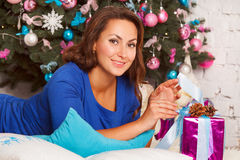 Happy young brunette woman opening gift box near christmas tree Stock Photography