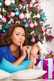 Happy young brunette woman opening gift box near christmas tree Stock Photos